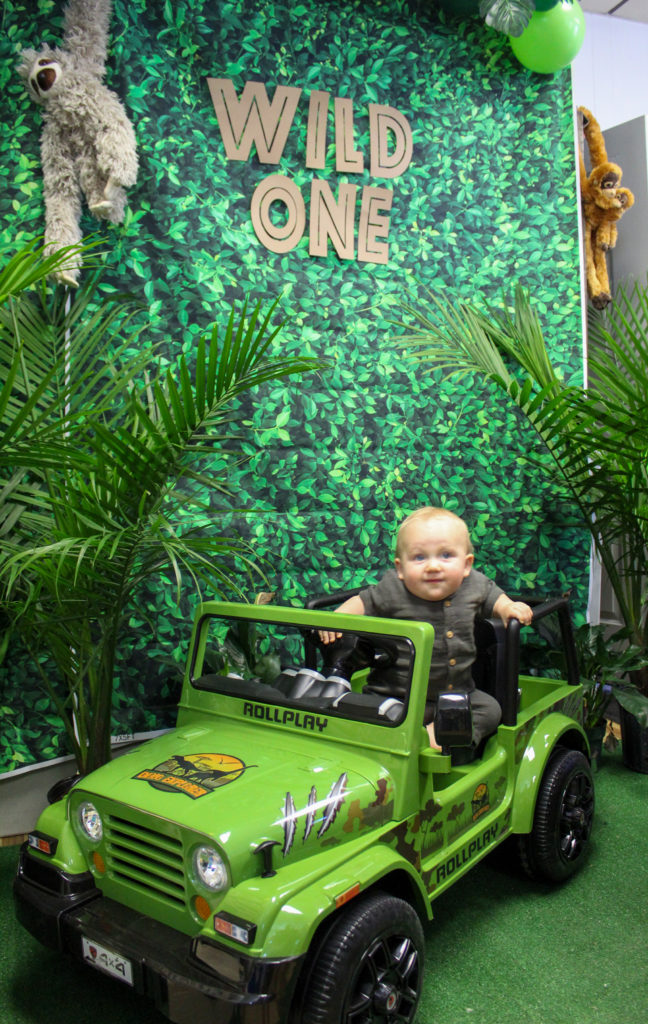 toddler in green jeep at WIld One first birthday party photoshoot