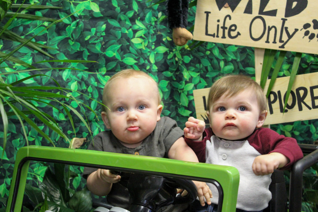 toddlers in green jeep at wild one first birthday party photoshoot