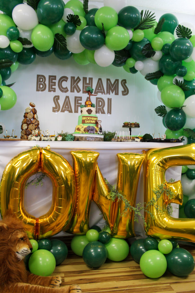 wild ONE safari themed first birthday party dessert table with green balloon arch