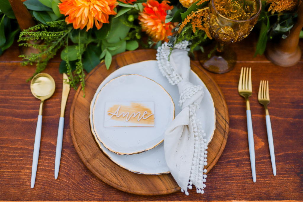 summer place setting on wooden charger plate with white linen napkin and plates