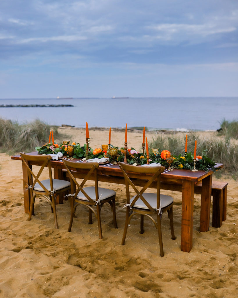 summer dinner party table set in sand next to water