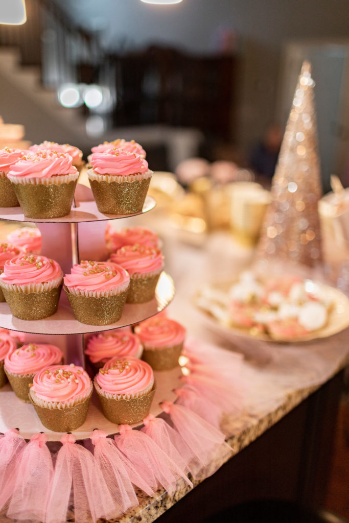 pink frosted cupcakes on tiered stand