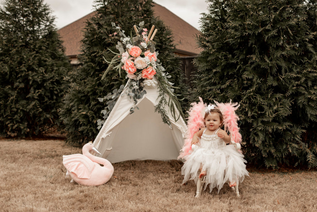 swan themed first birthday photoshoot with teepee and little girl
