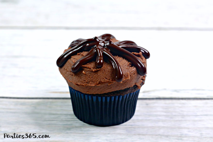 chocolate cupcake in navy blue cupcake liner with chocolate frosting and chocolate ganache