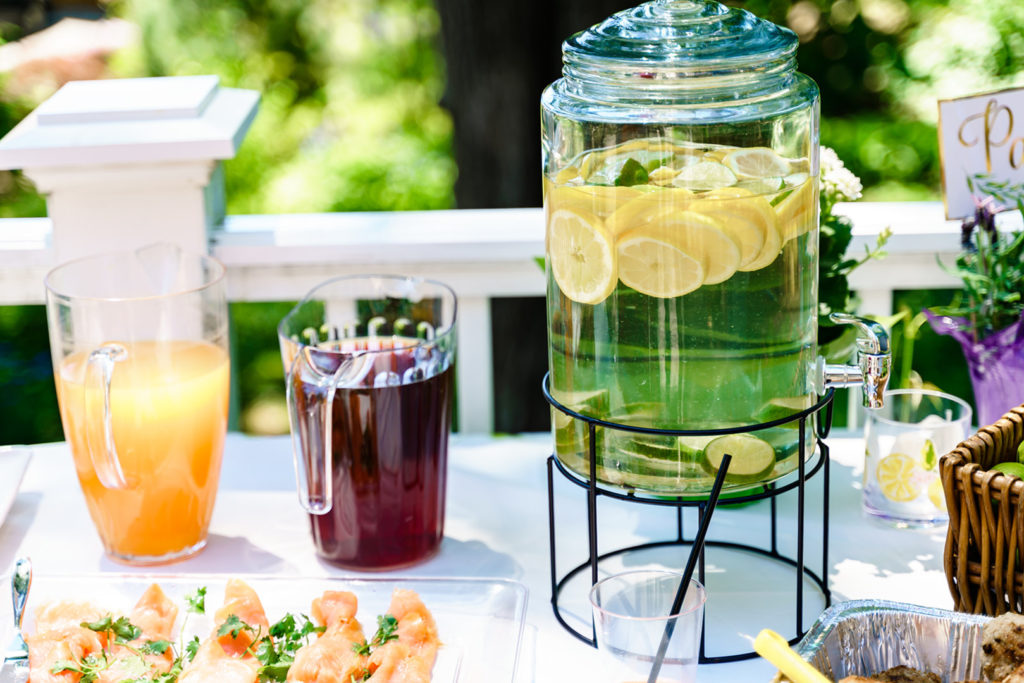 glass pitcher with fresh lemonade and sliced lemons