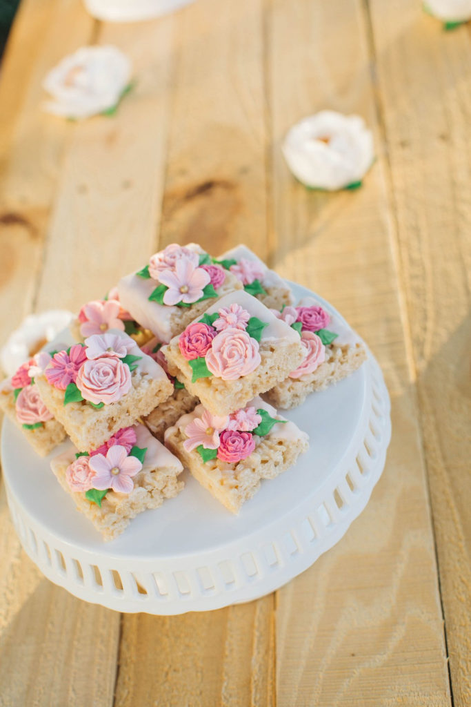 rice krispie treats decorated with flowers on white cake stand