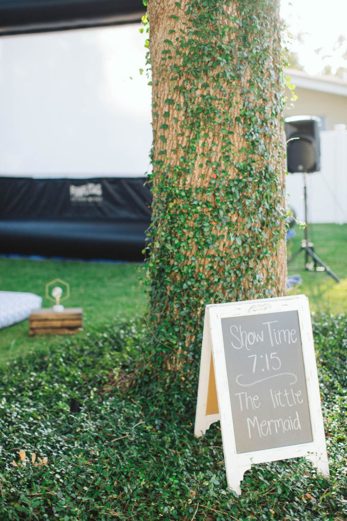 chalkboard sign by tree at outdoor movie night party