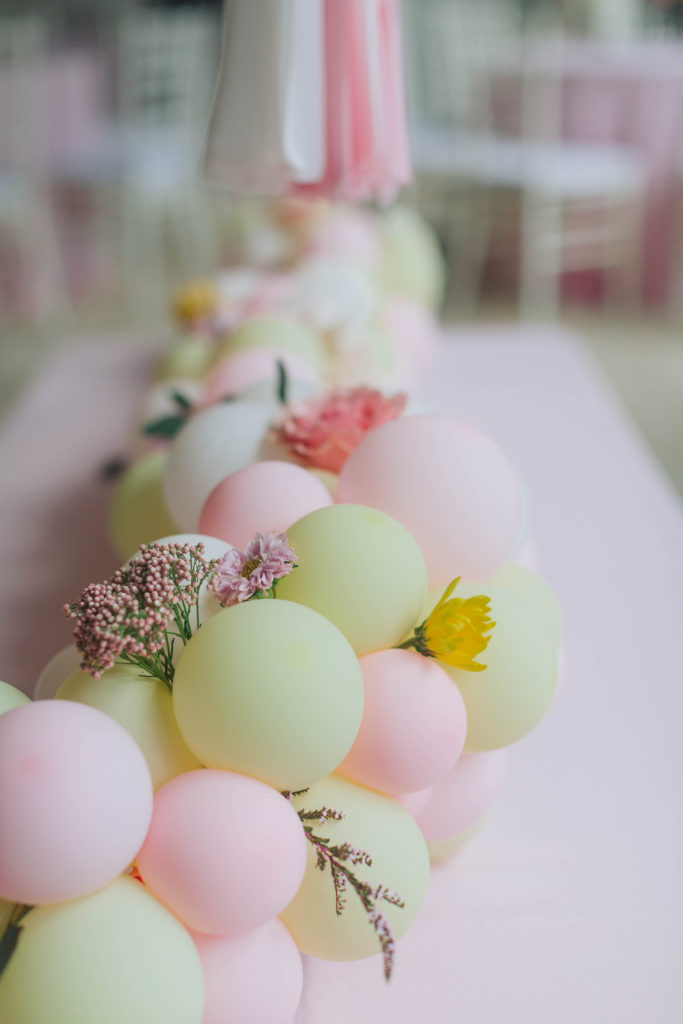 pink and yellow balloon garland centerpiece with flowers