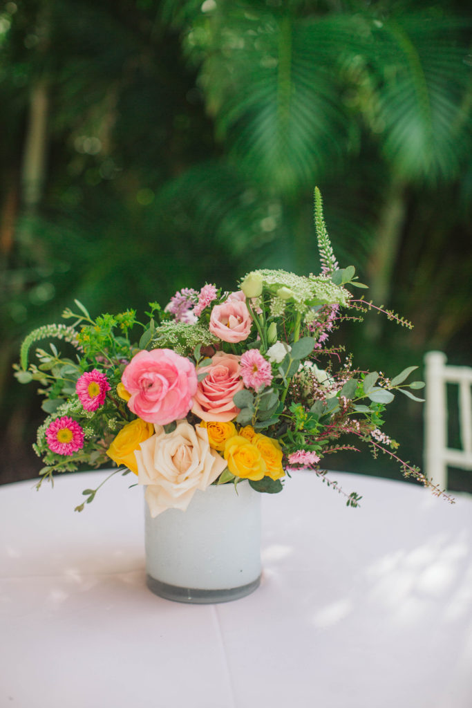 pink and yellow floral centerpiece in white vase on pink linen tablecloth