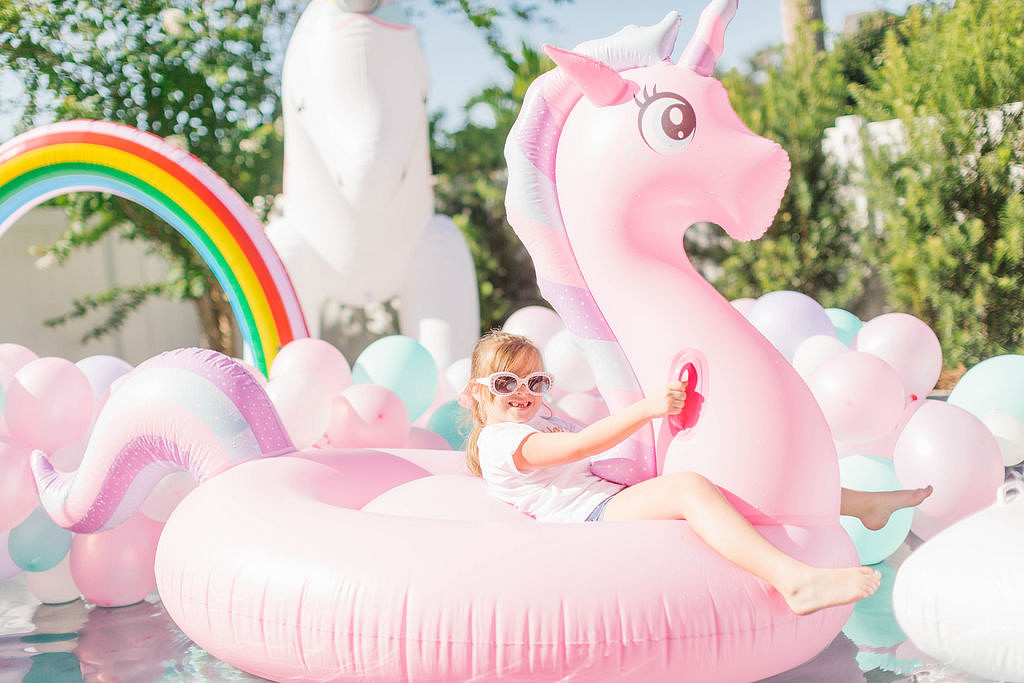 birthday girl on pink unicorn pool float at party
