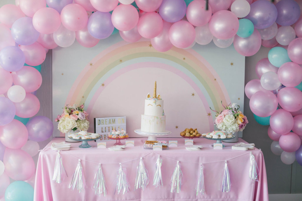 unicorn dessert table with balloon arch and rainbow
