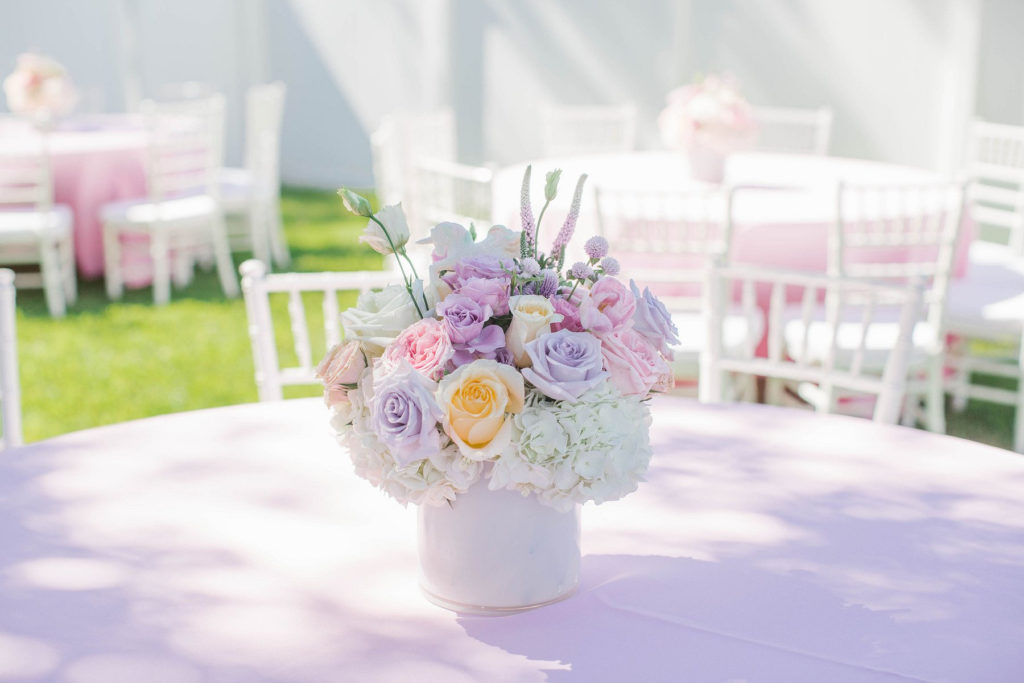 pastel pink and purple flower arrangement in white vase on pink linen tablecloth