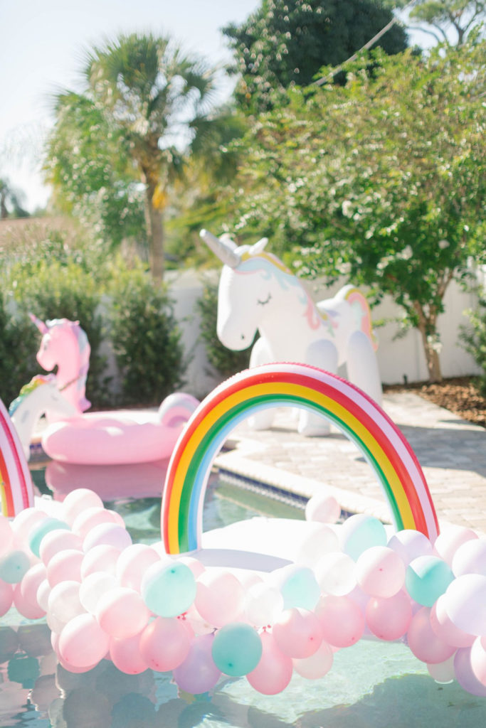 rainbow and unicorn pool floats in pool with balloons