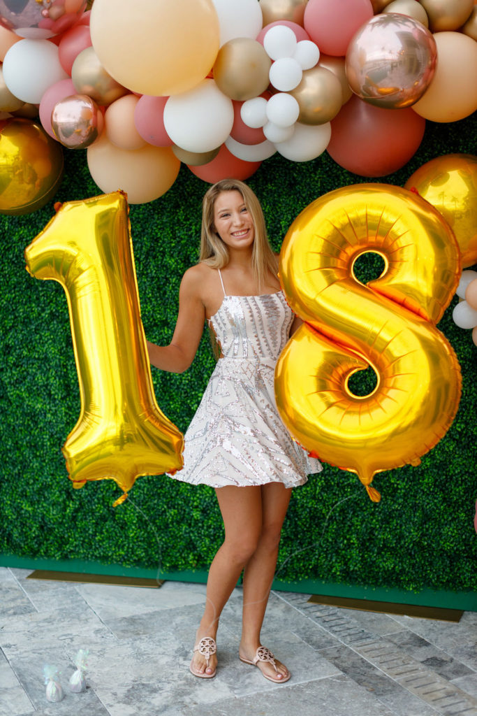 birthday girl holding gold 18 balloons