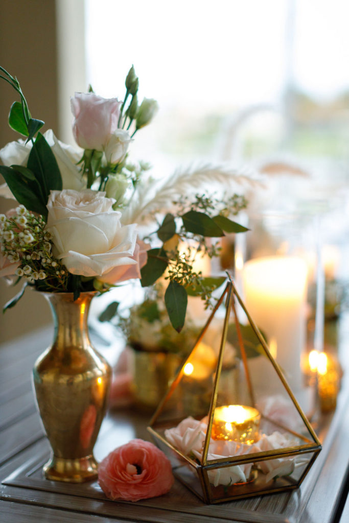 boho party decor featuring a gold terrarium and flowers