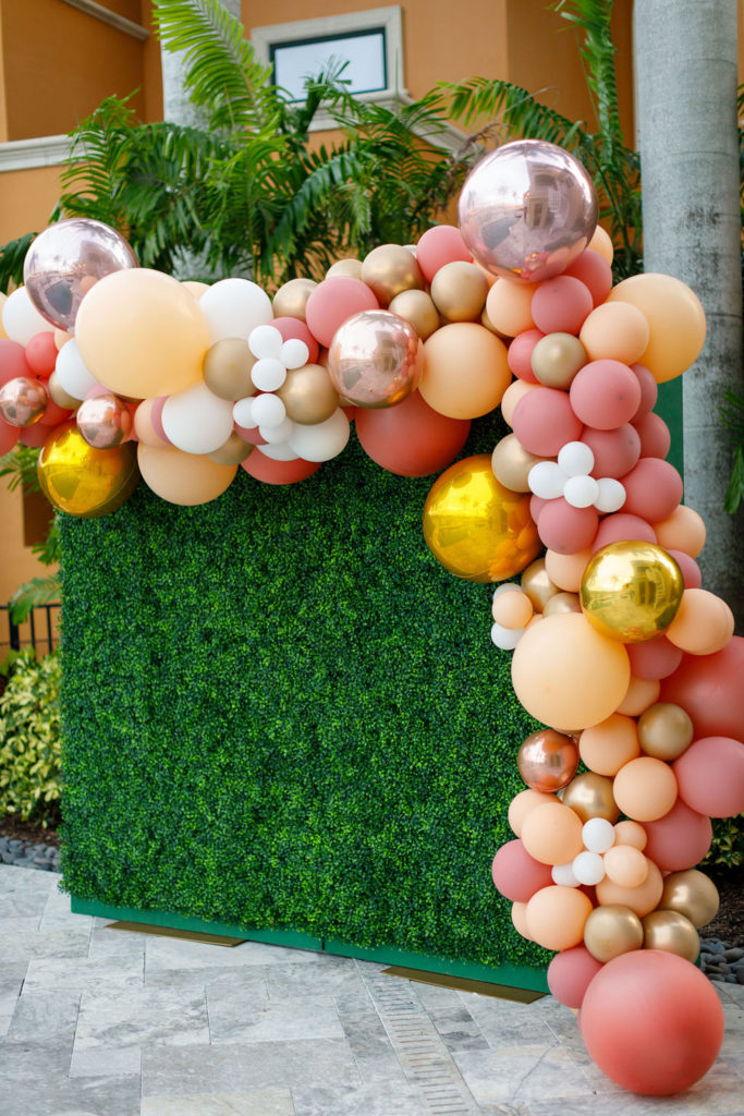 pink and gold balloon arch with green leaf backdrop