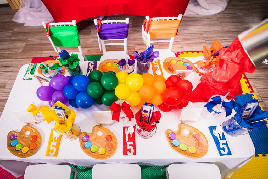 artist painting party table decor with rainbow balloons