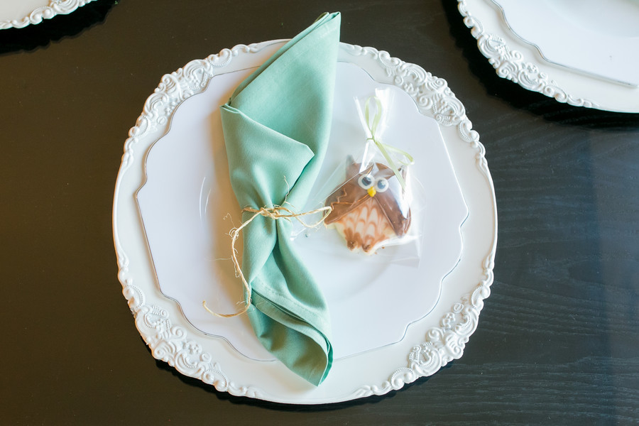 white charge plate and dinner plate topped with a napkin and owl cookie