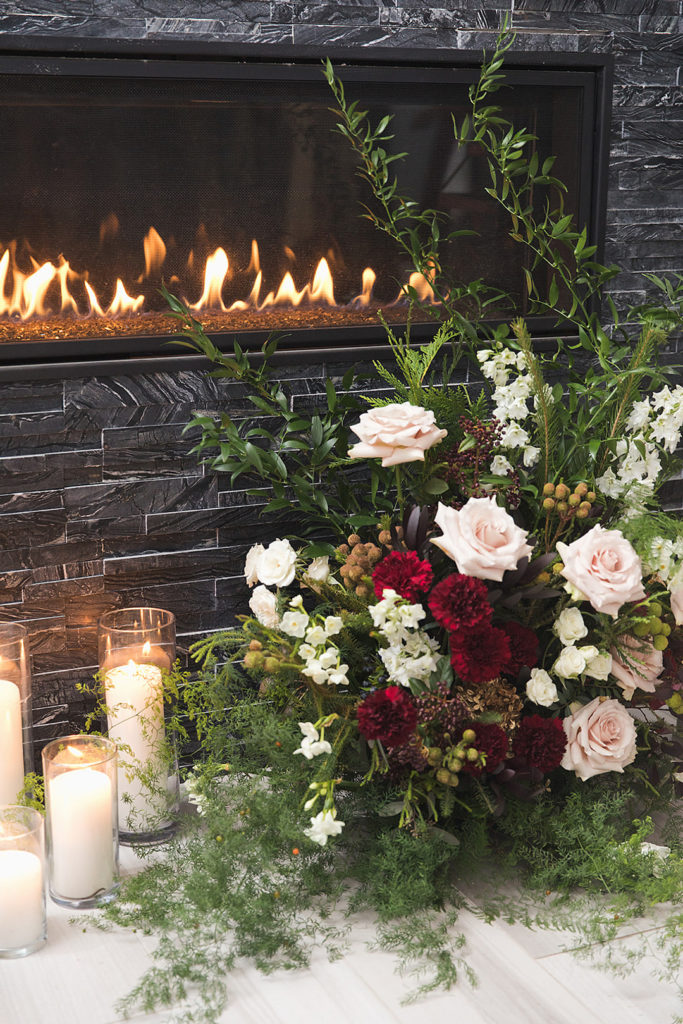 christmas party floral arrangement by fireplace