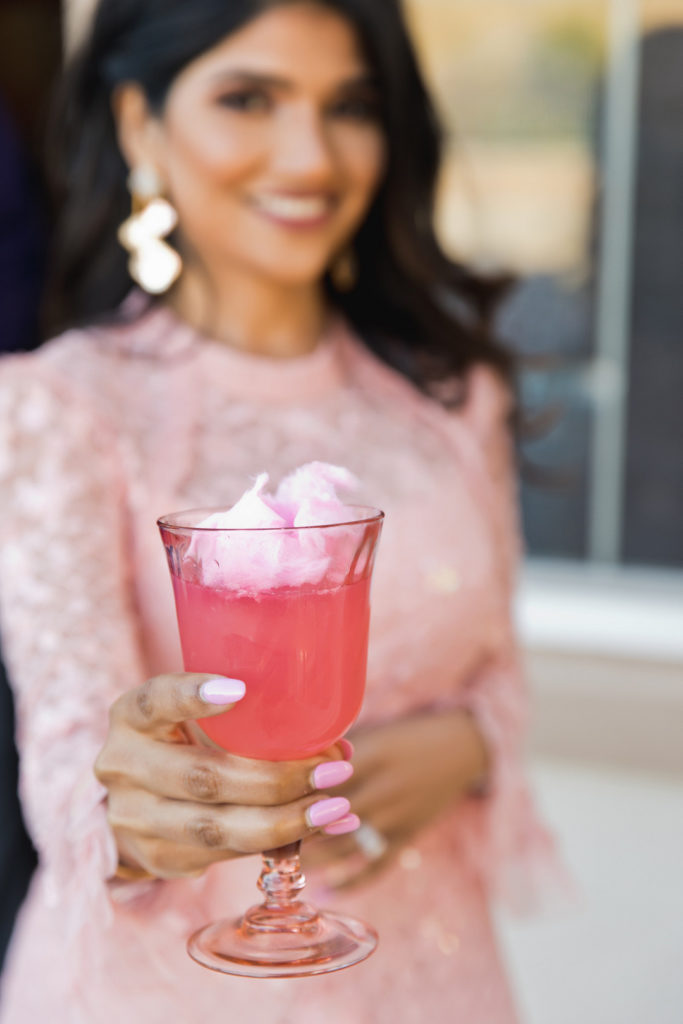 woman holding pink cocktail topped with cotton candy