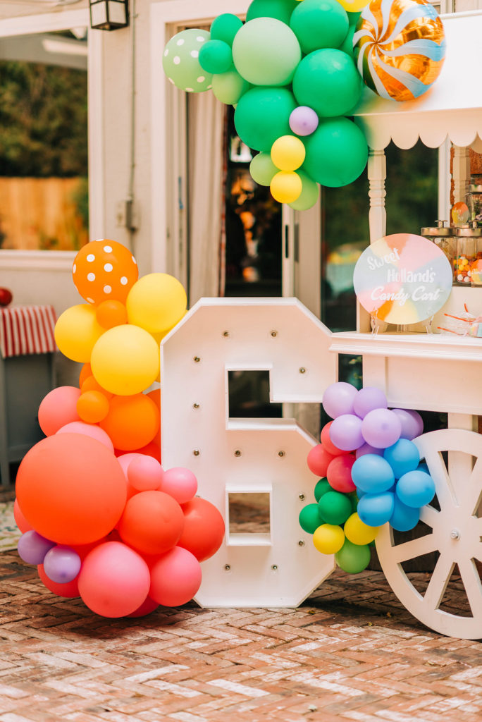 white candy cart at candy land birthday party with balloons