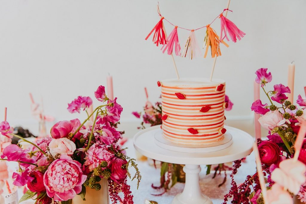 striped valentine's day cake with sugar lips and tassel banner