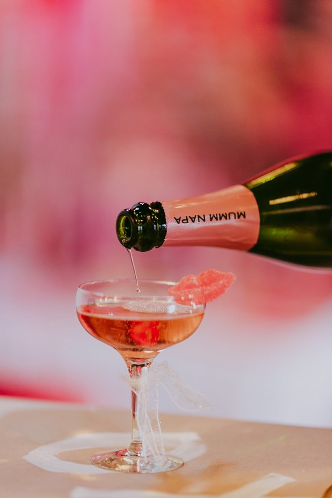 champagne pouring into a glass with red candy lips