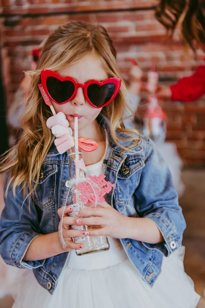 girl in red heart sunglasses sipping on a lemonade