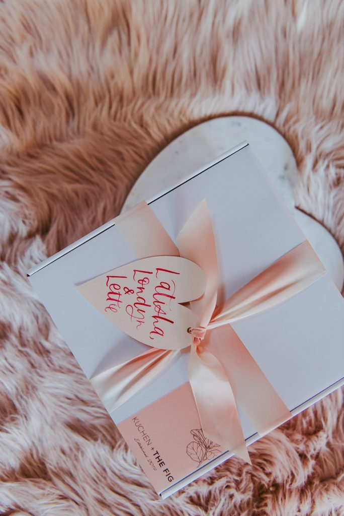 white party favor box wrapped with a pink satin ribbon