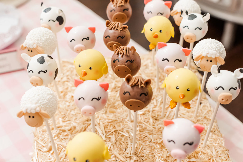 farm animal cake pops displayed in bales of hay