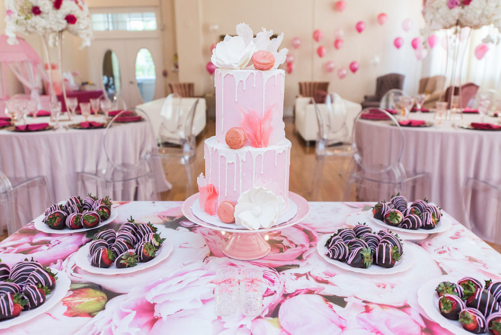 baby shower dessert table with pink cake and chocolate covered strawberries