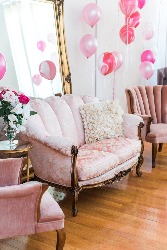 photo booth at baby shower with pink vintage seating and balloons