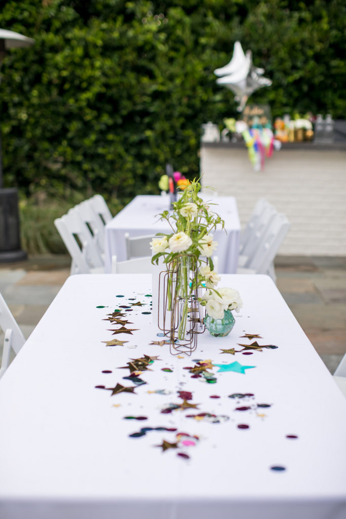 star confetti and floral centerpiece on white table
