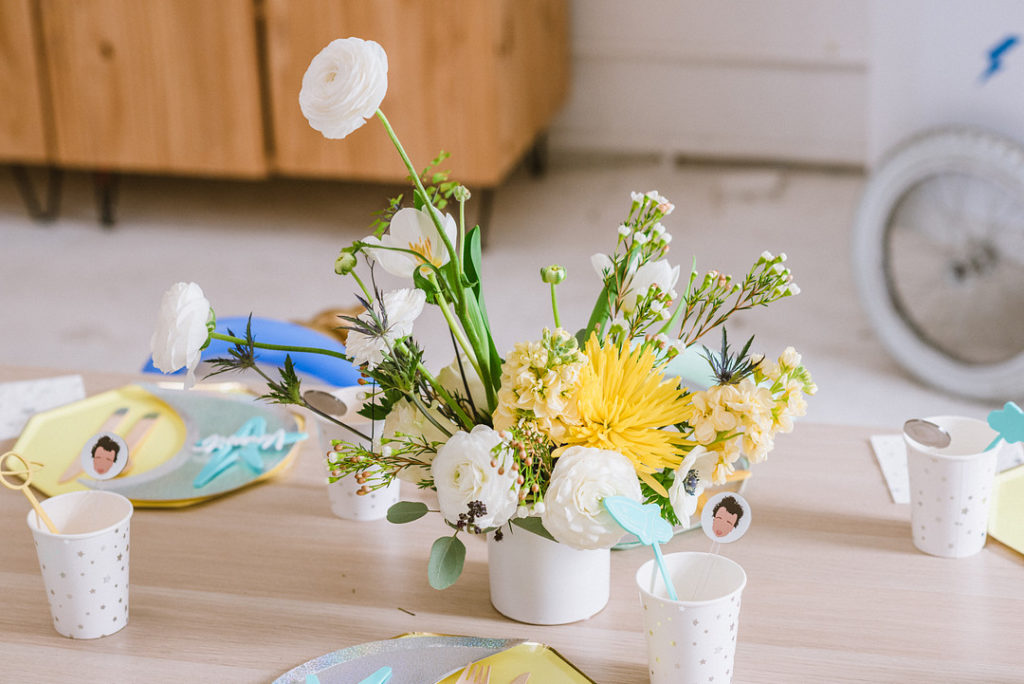white and yellow floral centerpiece at first birthday party