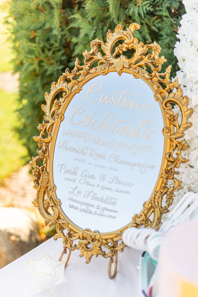 gold mirror cocktail sign at adoption shower