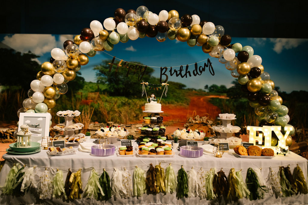 time flies airplane dessert table with balloon arch