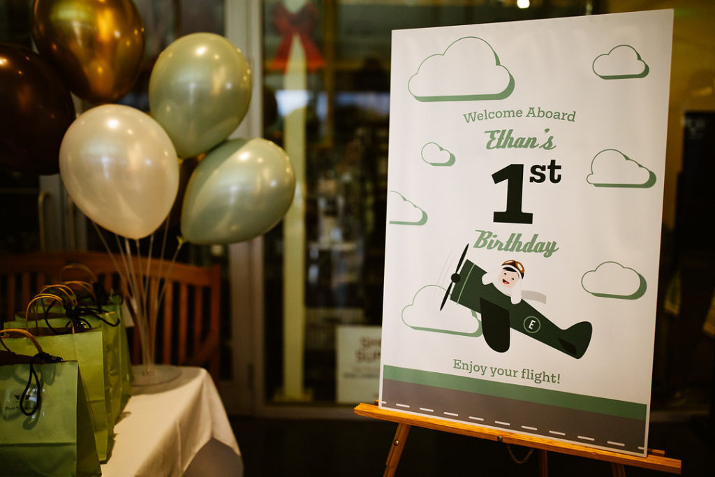 1st birthday welcome sign with green balloons