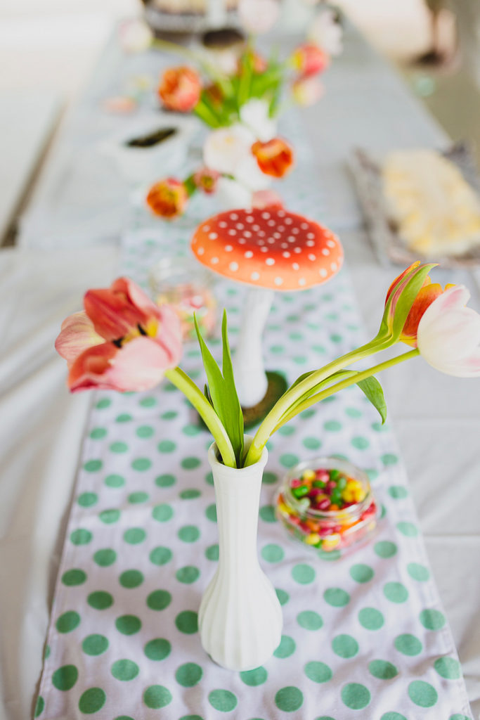 tulips and large mushroom in white vase at birthday party