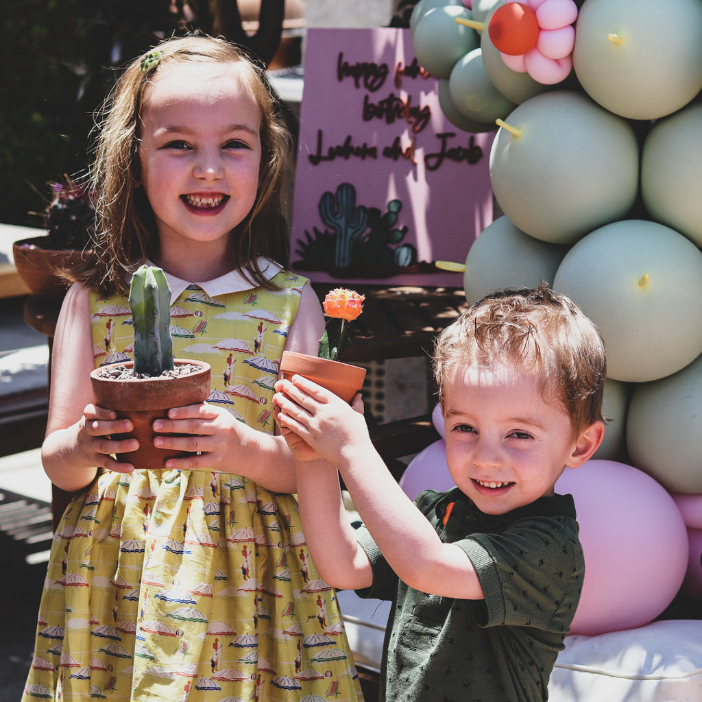 kids holding cactus party favors at birthday party
