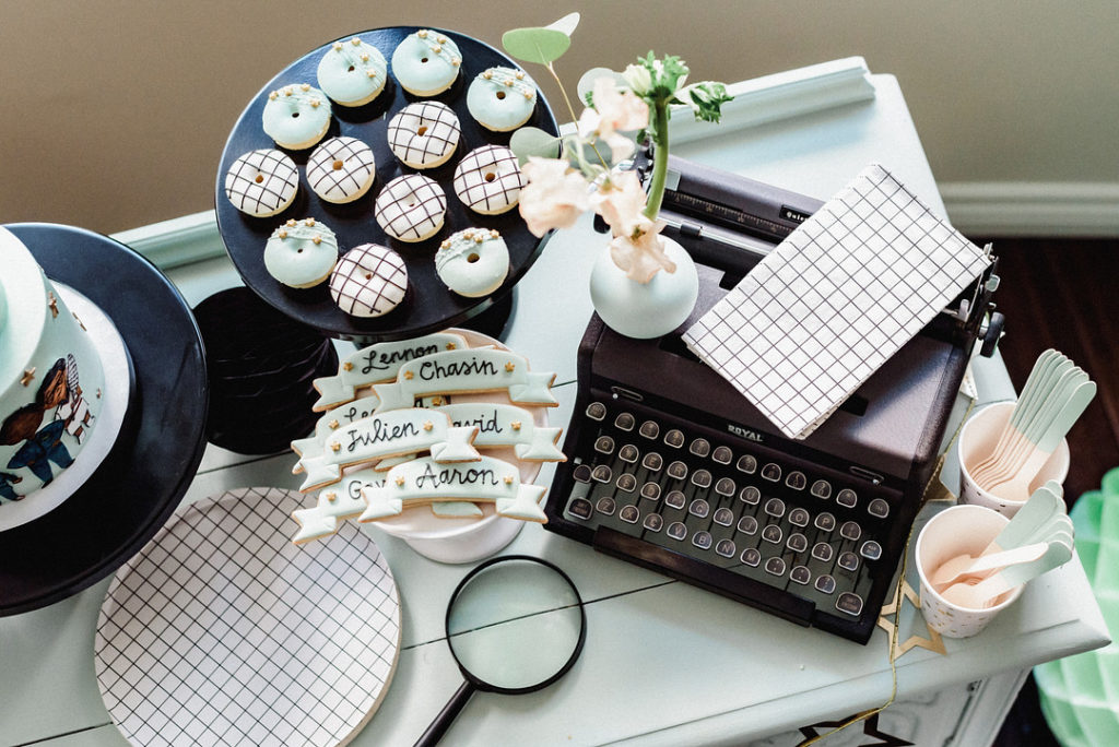 type writer and custom donuts at birthday party dessert table